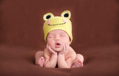Baby sleeping in frog hat