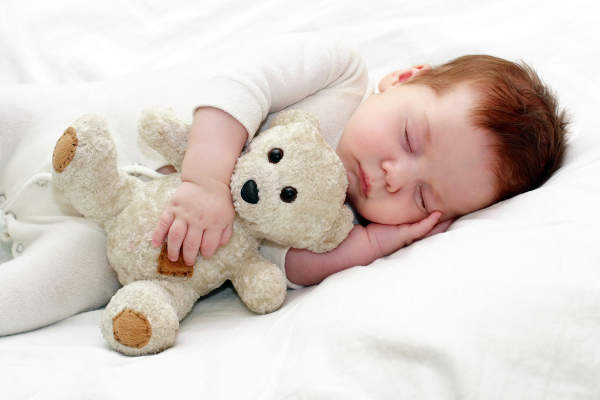 Baby sleeping with teddy