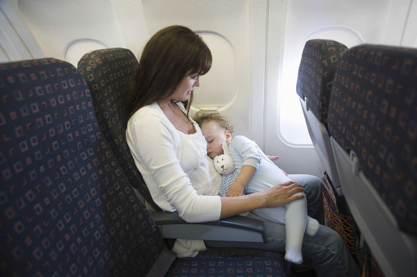 Toddler sleeping on mum in plane
