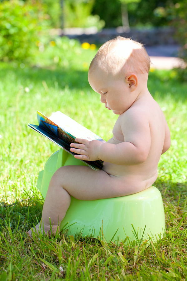 Outdoors on potty with book