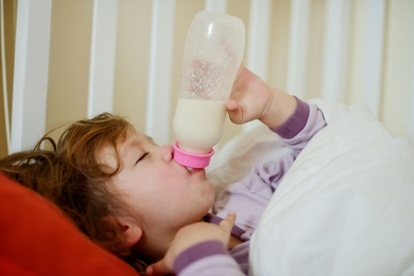 Toddler with bottle in bed