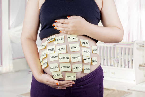Close up of pregnant belly with baby names choices