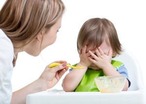 Mother trying to feed fussy toddler