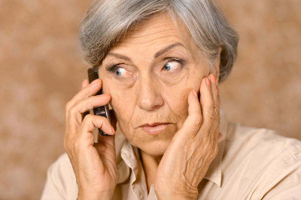 Portrait of worried elderly woman speaking on mobile against brown background