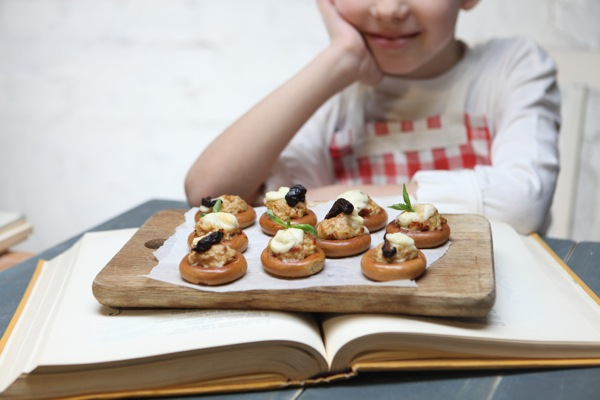 child with board of canapes