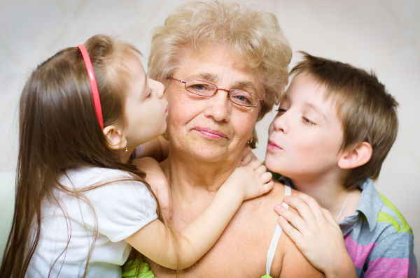 portrait of a cute grandchildren kissing grandmother