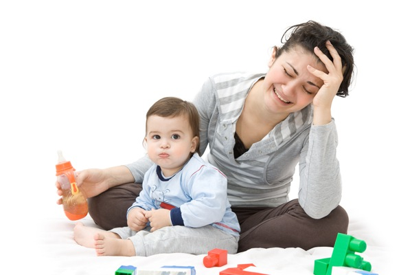 Tired mother and baby playing with toys