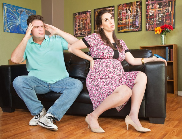 Frustrated husband next to pregnant wife with backache