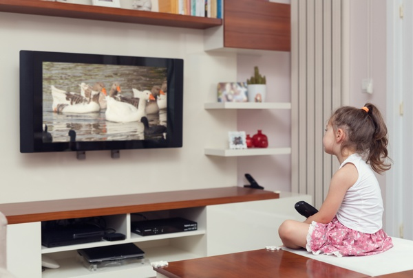 cute little girl having remote control and watching tv