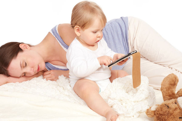 Child playing with your smartphone while mother is sleeping