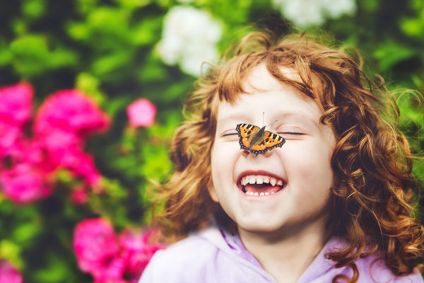 Laughing girl with a butterfly on her nose