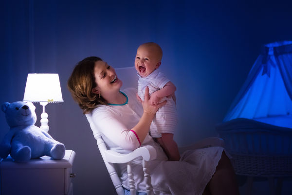 Mother and baby reading a book in dark bedroom