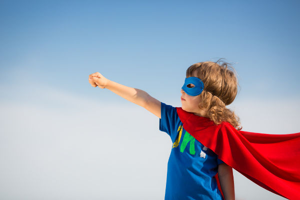 Superhero kid against blue sky background