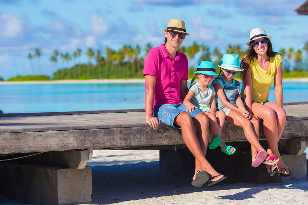 Beautiful family of four on beach during summer vacation