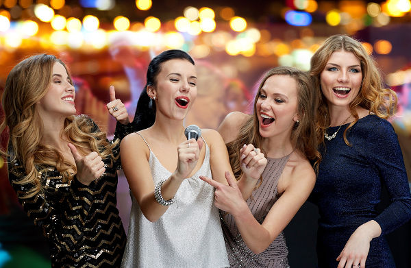 three women in evening dresses with microphone singing karaoke