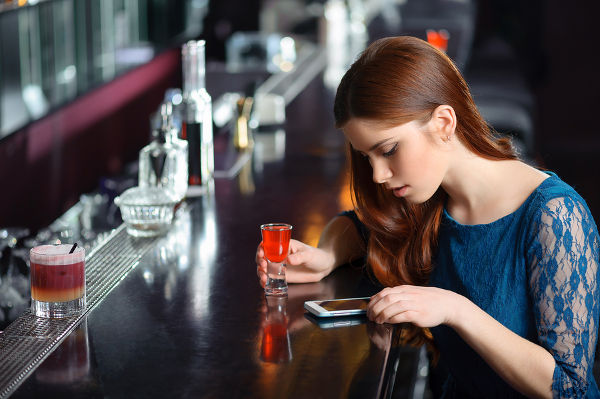 Young attractive woman looking at the screen of her phone sitting in the bar with a cocktail