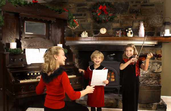 girls singing christmas carols in front of a fire.