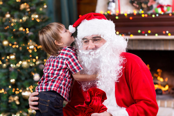 Santa Claus and child with presents at fireplace
