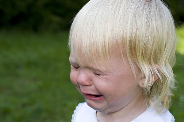 Blond child screaming with tears