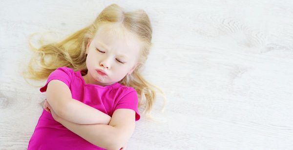 Very angry little girl lying on white wooden floor