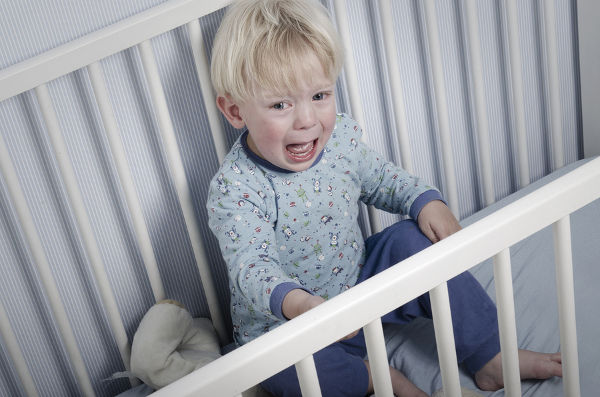 Crying boy in bed does not want to go to sleep. Very upset child.