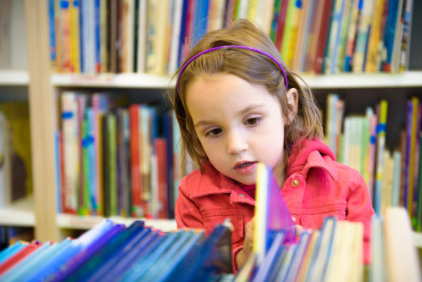 Little girl choosing book in library