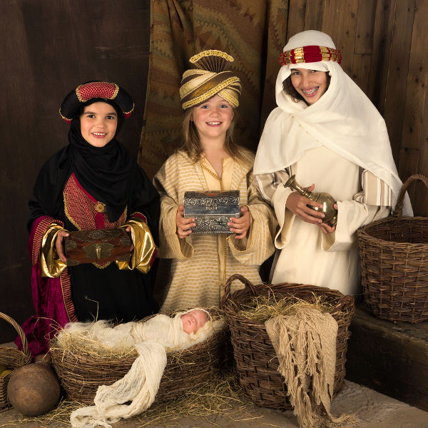 Teenager girls playing a live Christmas nativity scene (the baby is a doll)