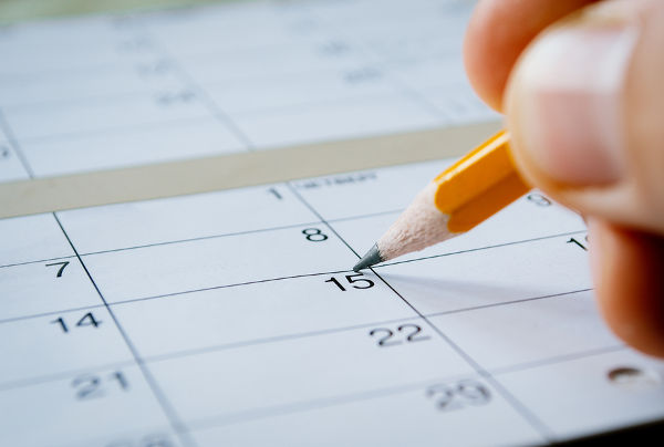 3-Person marking the date of the 15th with a pencil on a blank calendar