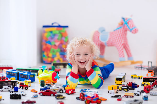 Funny curly toddler boy playing with his model car collection on the floor