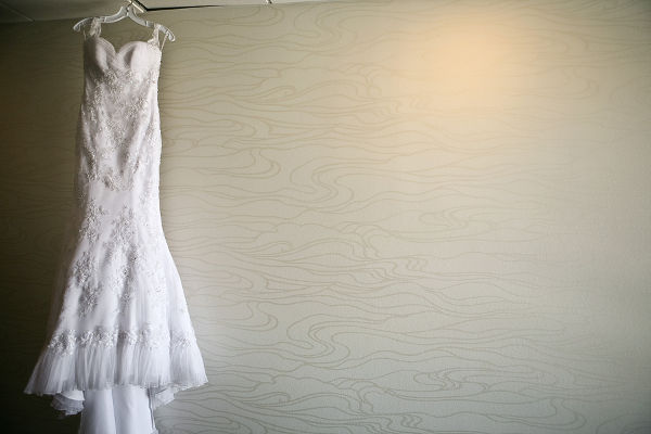 A white wedding dress hanging with a gray background