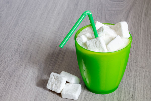 Green plastic glass with straw full of sugar and sugar cubes