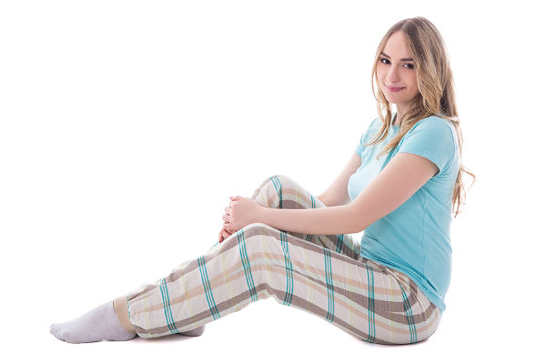 young beautiful woman in sleepwear sitting isolated on white background