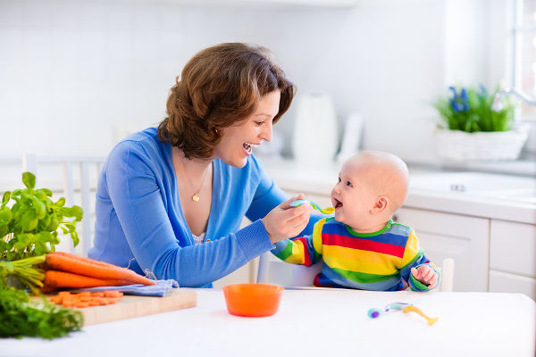 Mother feeding child healthy vegetables
