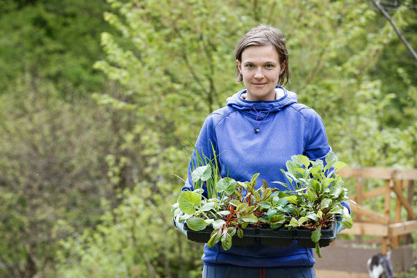 Proud and happy woman gardener bringing her homegrown seedlings