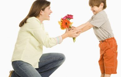 Son giving bouquet of flowers to mother.