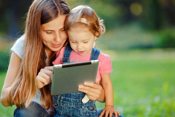 Beautiful mother and kid girl playing at tablet pc outdoors in fall