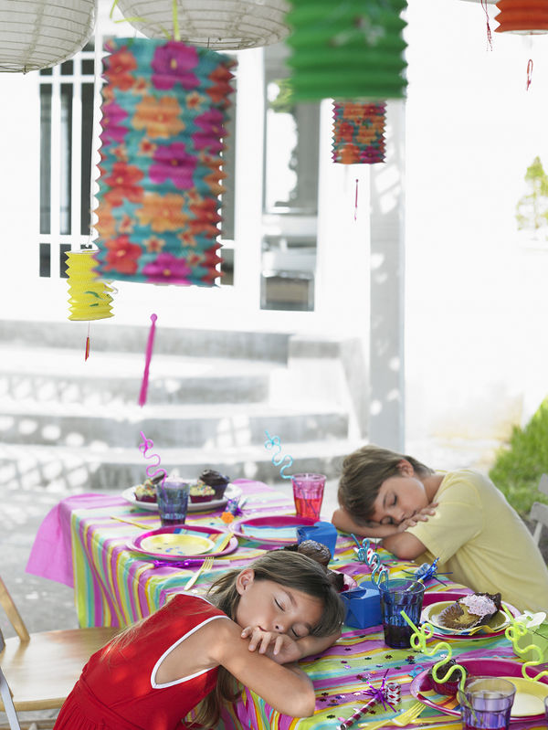Boy and girl sleeping at outdoor table after birthday party