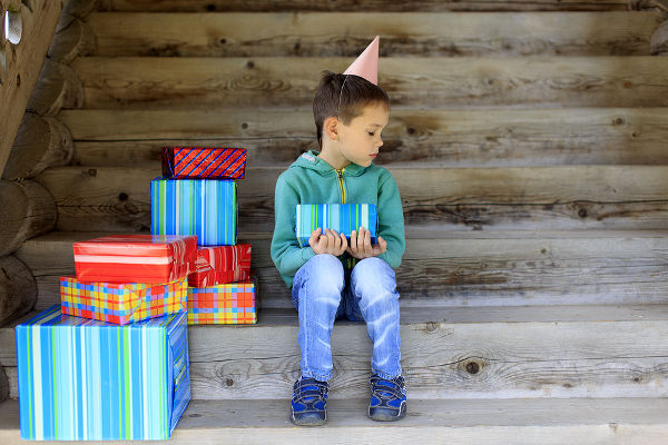 child sits alone surrounded by gifts and sad looking an empty place next to him