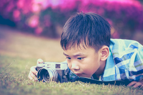 Asian boy taking photo by vintage film camera on blurred nature background at the day time