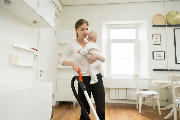 frustrated woman cleaning floor with baby