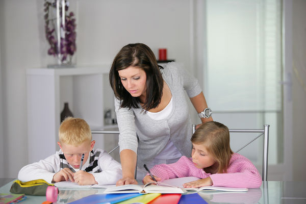 Portrait of young woman helping a boy and a girl in doing homework