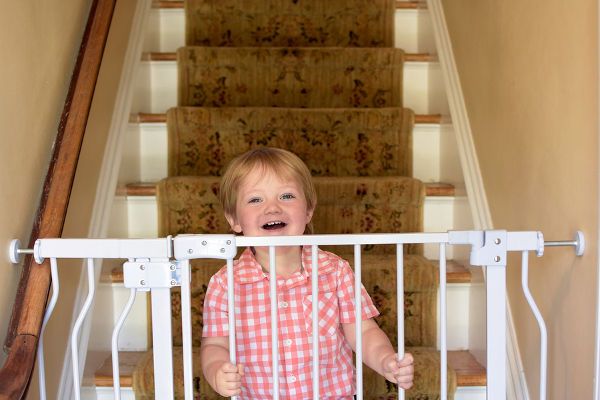 Adorable toddler boy standing on steps behind baby gate