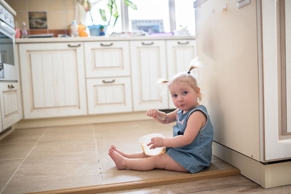 Girl with pigtails eating ice cream from a jar sitting on the floor in the kitchen