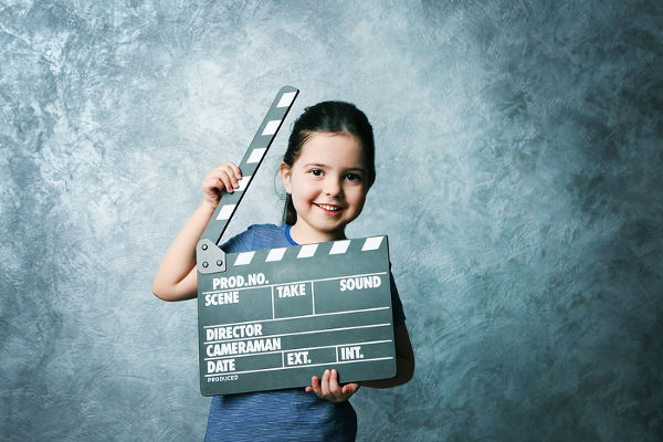 Little girl with a clapperboard on grey background