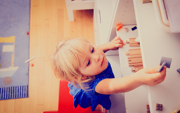 kids safety concept- little girl climbing on chair to get toy on top shelf