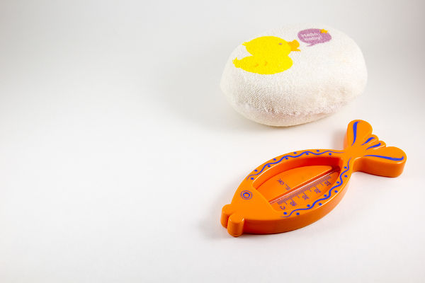 Baby sponge body and a thermometer for water on a white background