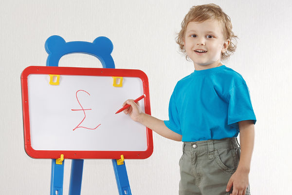 Little smiling boy drew pound sign on the whiteboard