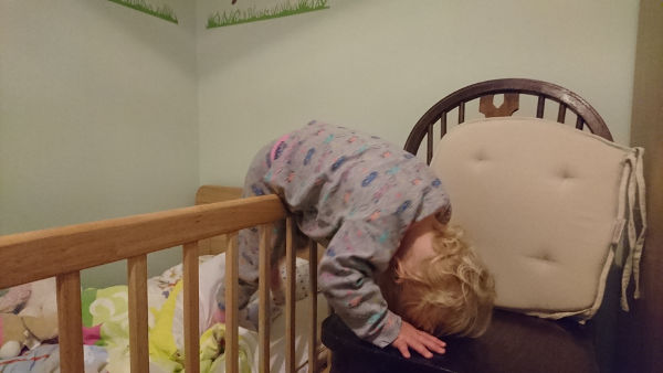 Baby climbing out of cot