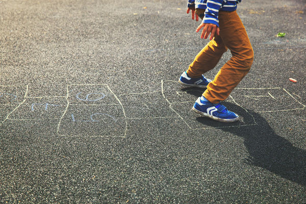 kid playing hopscotch on playground, kids outdoor activities