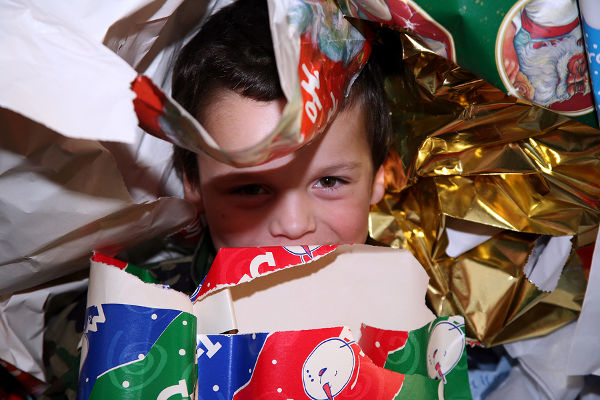 boy hiding in wrapping paper